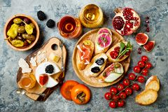 Appetizers table with italian antipasti snacks and wine in glasses. Brushetta or authentic traditional spanish tapas set. Cheese variety board over grey royalty free stock photo