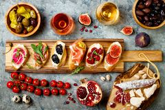 Appetizers table with italian antipasti snacks and wine in glasses. Brushetta or authentic traditional spanish tapas set stock images