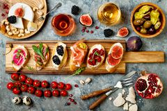 Appetizers table with italian antipasti snacks and wine in glasses. Brushetta or authentic traditional spanish tapas set. Cheese variety board over grey royalty free stock photography