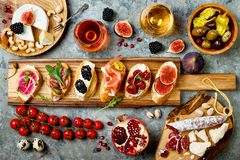 Appetizers table with italian antipasti snacks and wine in glasses. Brushetta or authentic traditional spanish tapas set. Cheese variety board over grey stock image