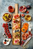 Appetizers table with italian antipasti snacks and wine in glasses. Brushetta or authentic traditional spanish tapas set. Cheese variety board over grey stock photos