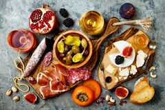 Appetizers table with italian antipasti snacks and wine in glasses. Brushetta or authentic traditional spanish tapas set. Cheese variety board over grey stock photo