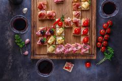 Appetizers table with italian antipasti snacks and wine in glasses. Brushetta or authentic traditional spanish tapas set, cheese v royalty free stock image
