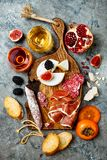 Appetizers table with italian antipasti snacks and wine in glasses. Charcuterie and cheese board over grey concrete background. royalty free stock images