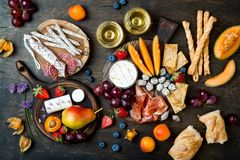 Appetizers table with italian antipasti snacks and wine in glasses. Cheese and charcuterie variety board over rustic wooden table royalty free stock photo