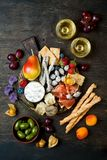 Appetizers table with italian antipasti snacks and wine in glasses. Cheese and charcuterie variety board over rustic wooden table. Appetizers table with italian royalty free stock images