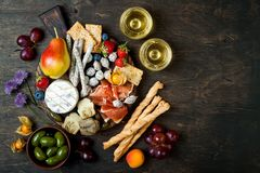 Appetizers table with italian antipasti snacks and wine in glasses. Cheese and charcuterie variety board over rustic wooden table. Appetizers table with italian stock photography