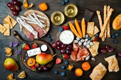 Appetizers table with italian antipasti snacks and wine in glasses. Cheese and charcuterie variety board over rustic wooden table. Appetizers table with italian royalty free stock image