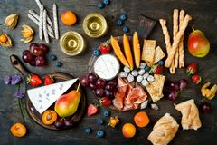 Appetizers table with italian antipasti snacks and wine in glasses. Cheese and charcuterie variety board over rustic wooden table. Appetizers table with italian stock photos