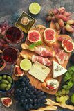 Appetizers table with italian antipasti snacks and wine in glasses . Traditional italian bread sticks grissini with prosciutto ham royalty free stock photos