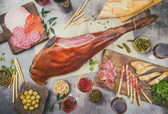 Appetizers table with spanish iberian whole ham jamon serrano, snacks, olives and red and rose wine. Flate lay. Top view stock photography