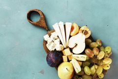 Appetizers table wine Fruit cheese wooden board background copy space. Appetizers table for wine. Fruit and cheese on wooden board on stone background with copy stock images