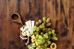 Appetizers table wine Fruit cheese wooden board. Set appetizers table and wine. Fruit and cheese on wooden board. Wine appetizers royalty free stock image