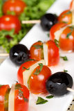 Appetizers with tomato, cheese and olives. Vertical shot Stock Photos