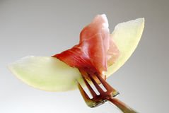 Appetizing. Melon with ham on a fork Royalty Free Stock Images