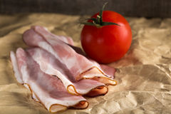 Appetizing bacon on paper. Close-up of some appetizing bacon on paper and one cherry tomato Royalty Free Stock Photography