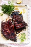 Appetizing baked glazed veal or pork ribs served with lemon and herbs. stock photography