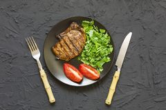 Appetizing barbecue steak with a barbecue sauce and served with fresh tomatoes on a black plate. Royalty Free Stock Images