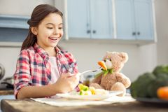 Inspired girl feeding her toy with healthy food. So appetizing. Beautiful exuberant dark-haired little girl smiling and feeding her toy with healthy food while Royalty Free Stock Photography
