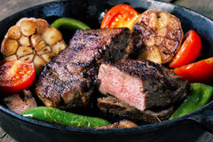 Appetizing beef steak in frying pan with vegetable garnish. Appetizing beef steak in a frying pan with vegetable garnish. The concept of healthy eating Royalty Free Stock Images
