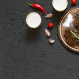 Appetizing beef steaks, beer and rosemary. top veiw. Appetizing beef steaks, beer and rosemary on a black stone background Royalty Free Stock Photo