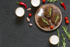 Appetizing beef steaks, beer and rosemary. top veiw. Appetizing beef steaks, beer and rosemary on a black stone background Stock Photography