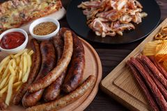 Appetizing beer snacks close up. Grilled sausages with french fr royalty free stock photo