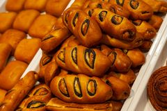 Appetizing big golden buns with poppies in the form of rolls, co royalty free stock photo