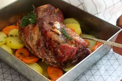 Appetizing boiled pork with potatoes and carrots, baked in a tin pan. Rustic style. stock image
