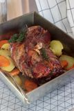 Appetizing boiled pork with potatoes and carrots, baked in a tin pan. Rustic style. stock photo