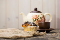 Appetizing breakfast fresh cupcake. With aromatic black coffee in brown cup and beautiful teapot near sackcloth napkin on wooden table light background indoor royalty free stock photo