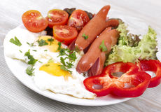 Appetizing breakfast. With fried eggs fried eggs and fried sausages Stock Images