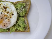 Appetizing bruschetta with egg and avocado on a plate royalty free stock image