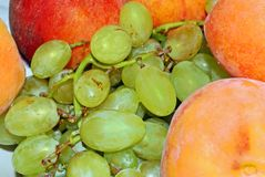 Appetizing bunch of grapes and peach. Appetizing bunch of green grapes and same peach, green and red color Royalty Free Stock Images