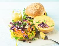 Appetizing burger from fresh sesame buns and raw vegetables and young sprouts on a blue light background. Vegetarianism. stock photography