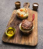 Appetizing burger only meat and eggs and butter, with rice and vegetables,  spices on vintage cutting board. Appetizing burger only meat and eggs and butter Royalty Free Stock Images