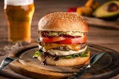 Cheeseburger, made from rye bun with tomato slice and melted cheese on a roasted beef, and lettuce leaf on a wooden royalty free stock image