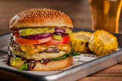 Cheeseburger, made from rye bun with tomato slice and melted cheese on a roasted beef, and lettuce leaf on a wooden stock image
