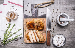 Appetizing chicken cooked in mustard sauce and cut into slices on a cutting board a knife, herbs, salt and pepper unmilled on Royalty Free Stock Image