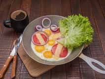 Appetizing classic breakfast. Eggs with tomatoes, cheese, onions, salad and fresh coffee on a wooden table royalty free stock image