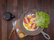Appetizing classic breakfast. Eggs with tomatoes, cheese, onions, salad and fresh coffee on a wooden table royalty free stock photo