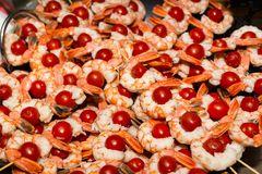 Appetizing cooked shrimps with tomatoes on skewers at food festi. Val, food and beverage concept Stock Image