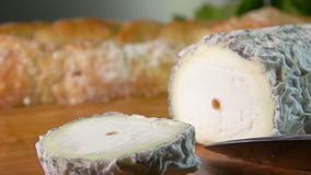 Appetizing crust cut with a knife from goat cheese stock footage