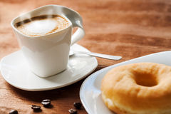 Appetizing cup of coffee with doughnut. Royalty Free Stock Photos