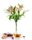 Appetizing cupcake on a dish, tea and alstroemeria Stock Image