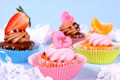 Appetizing cupcakes with angel, heart, tangerine, strawberry Stock Photos