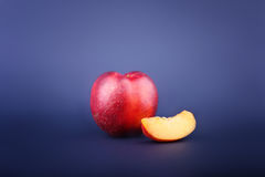 An appetizing cut nectarine on a dark blue background. Sweet and juicy nectarine slice. A whole nectarine for a light snack. Stock Images
