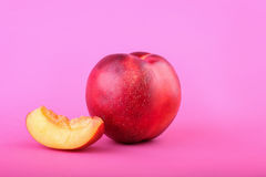 An appetizing cut nectarine on a dark blue background. Sweet and juicy nectarine slice. A whole nectarine for a light snack. Stock Photo
