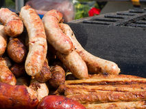 Appetizing delicious fried meat frankfurters sausage on a barbecue grill outdoors. Royalty Free Stock Images