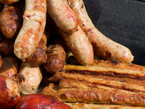 Appetizing delicious fried meat frankfurters sausage on a barbecue grill outdoors. Stock Images